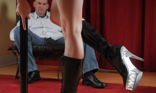 Legs of stripper with man watching in background