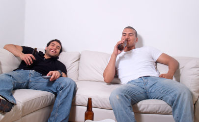 2 guys laughing, drinking beer and watching TV